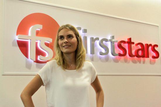 Digitale Leute - Anne Gradler - firststars - Anne posiert vor dem Logo der SEA-Agentur.