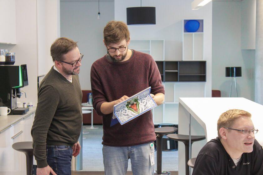 Digitale Leute - Tobias Röver - Microsoft - Tobias bespricht sich mit einem Kollegen, dem er etwas auf seinem Surface zeigt.