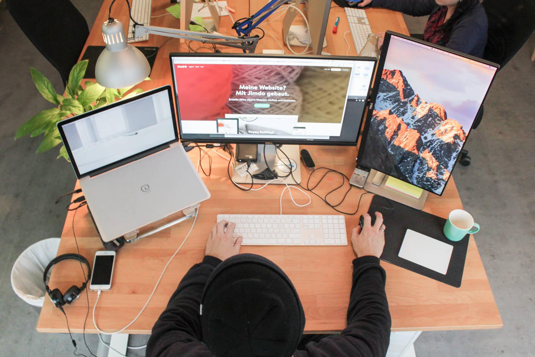 Ingo Ellerbusch - Jimdo - Ingos Arbeitsplatz von open: Sein MacBook Pro, ein 27 Zoll Monitor und ein vertikaler, für den Code. Dazu Tastatur und Maus.