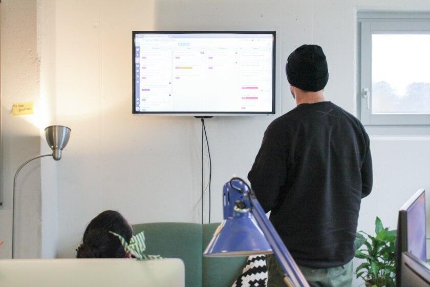 Ingo Ellerbusch - Jimdo - Das tägliche Standup häkt Ingo und sein Marketing Design Team vor diesem monitor ab.