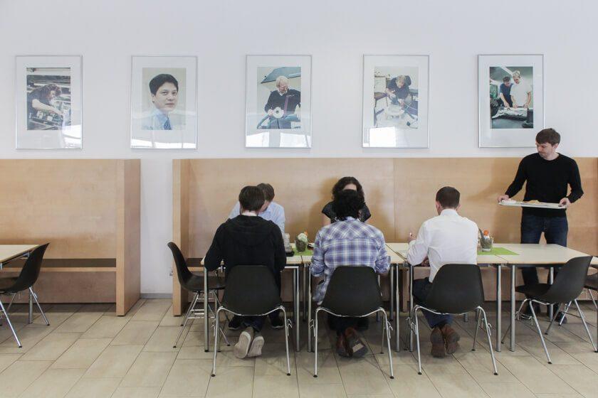 Digitale Leute - Mario Wallmeyer - Vorwerk - Das Team der Abteilung Softwareentwicklung isst unter historischen Bildern von Vorwerk.