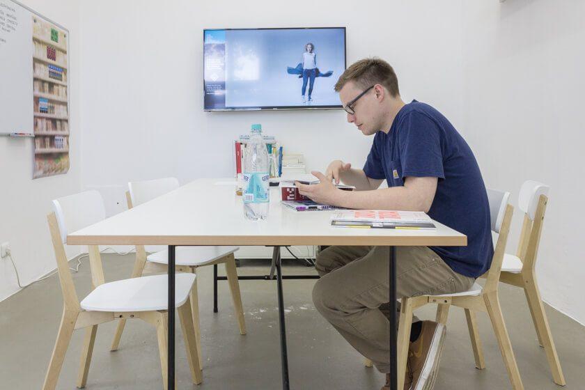Digitale Leute - Lukas Höh - Fluur - Lukas sitzt im Besprechungsraum in Köln Mülheim und liest Magazine.