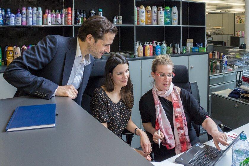 Digitale Leute - Dr. Nils Daeke - Henkel - Kolleginen von Nils Daeke zeigen auf wichtige Zahlen im Marketing.