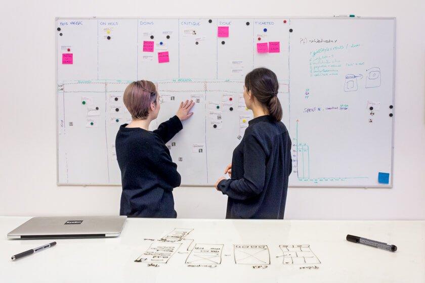 Digitale Leute - Adrienne Ossko - EyeEm - Adrienne geht mit einer Kollegin die Prozesse der Produktentwickliung durch.